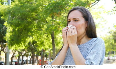 Adult woman sneezing in a park - Adult woman suffering flu...