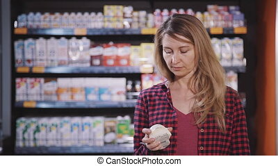Adult woman standing in supermarket with fresh food in hands...