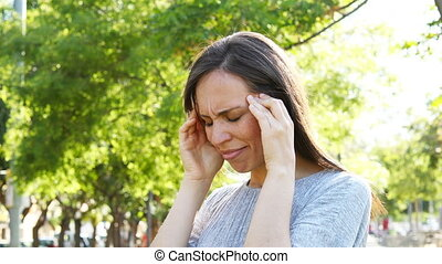 Adult woman suffering migraine in a park - Adult woman...