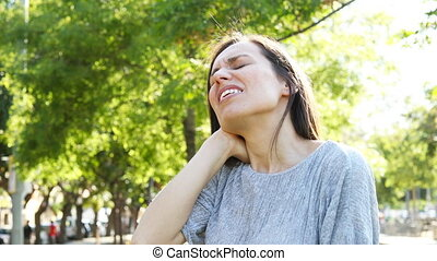 Adult woman suffering neck ache in a park - Adult woman...