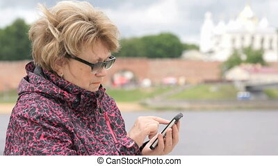 Adult woman tourist holding a smartphone outdoors - Adult...