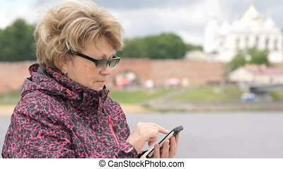 Adult woman tourist holding a smartphone outdoors
