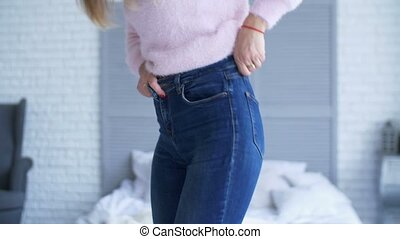Adult woman trying to zip up tight jeans at home -...