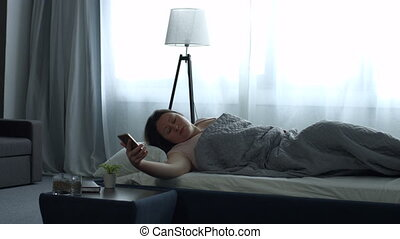 Adult woman waking up with mobile alarm clock