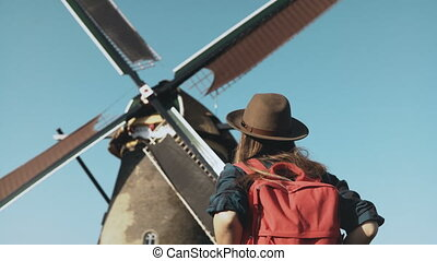 Adult woman walks up to a rustic windmill. Incredible...