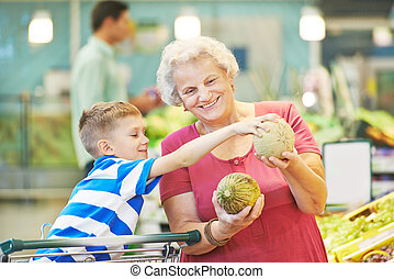 Adult woman with child shopping fruits