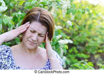 adult woman with  headache about bird cherry blossoms in spring