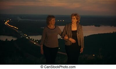Adult women mother and daughter walks on the hill talking at summer sunset