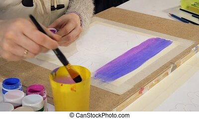 Adult women paint with colored acrylic paints in an art...