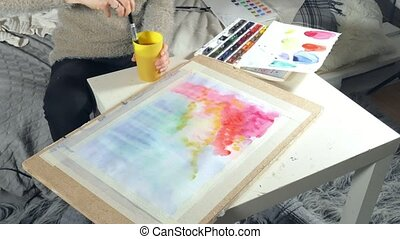 Adult women paint with colored watercolor paints in an art...