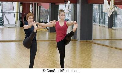 Adult women practice oriental asanas in modern studio....