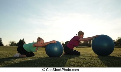 Adult women working out in park with fitness balls