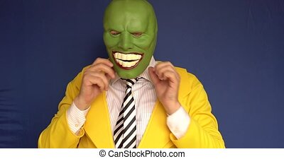 Adult takes off mask blooms with a lovely smile background blue bright daylight shooting front clothing yellow