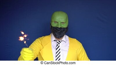 A large worker takes off his mask blooms with a wonderful smile. White daylight. Dark mask. Blue eyes. Clothes. Yellow.