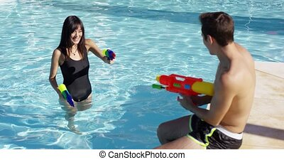 Adults shooting shooting water guns at each other