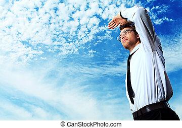 advancement - Successful business man standing over blue sky...