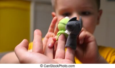 Finger toys background. Child playing with puppet dolls with parent, nurse, father. Preschooler with father playing together indoors. Home video style. Study via game