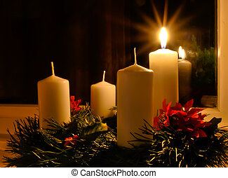 Advent wreath with a lighted candle placed on the window