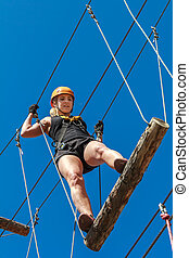 Adventure climbing rope park - a young woman in protective gear passes the track on a rope simulator. training mountaineers in the mountains