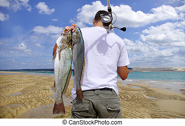 Adventure fishing - A surf fisherman with two big saltwater...