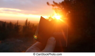Adventure idea. Book with the inscription and sunset in the forest.