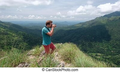 Adventure photographer with camera shoots while standing in...