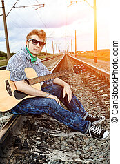 adventure - Portrait of a handsome young man with a guitar ...