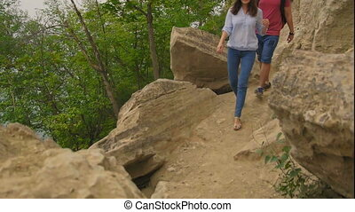 Adventure traveling: couple - young woman and man walk on...