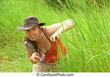 Adventure Woman Hides in Grass pretending to be an Animal