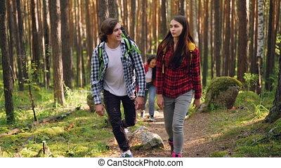 Adventurous friends are trekking in wild woods with...