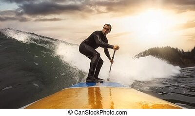 Adventurous Man Surfing the waves at the Pacific Ocean in Tofino, Vancouver Island, British Columbia, Canada. Dramatic Colorful Sunset Sky. Extreme sport