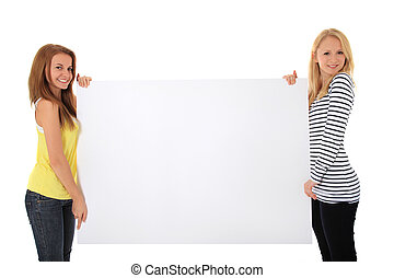 Two young women holding blank white sign with plenty copy space. All on white background.