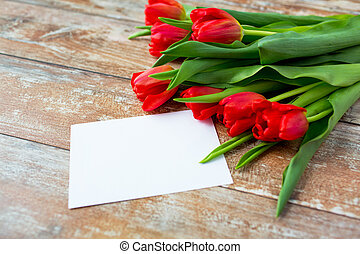 close up of red tulips and blank paper or letter -...