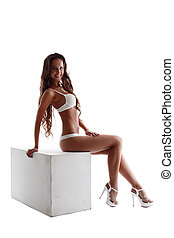 Advertising underwear. Slim model sitting on cube