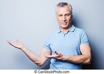 Advertising your product. Confident senior man in casual looking at camera and smiling while pointing away and standing against grey background