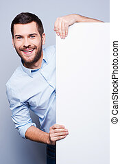 Advertising your product. Handsome young man leaning at copy space and smiling while standing against grey background