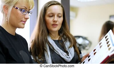 Adviser-cosmetician recommends color of hair-dye to woman to client