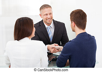 Advisor Shaking Hand With Couple - Smiling financial advisor...