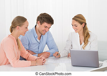 Advisor Showing Document To Couple - Happy Female Advisor...