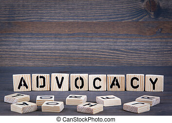 Advocacy word written on wood block. Dark wood background with texture
