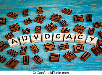 advocacy word written on wood block. Wooden alphabet on a blue background