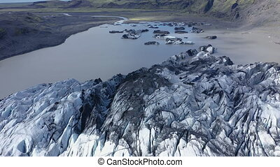 Aerial 4k drone high angle view of the melting Solheimajokull glacier in Iceland. Climate change, melting glaciers, global warming concept