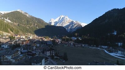 Aerial above village at winder with mountains peak snow view. Drone fly over alpine dolomites snowy Italy Pieve di Cadore