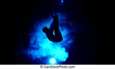 Aerial acrobat man on circus stage. Silhouette on a blue background.