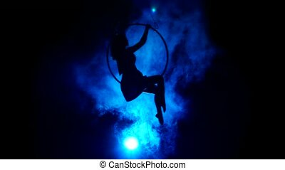 Aerial acrobat woman on circus stage. Silhouette on a blue...