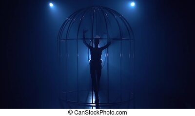 Aerial acrobatics on a rotating hoop in cage in a dark room. Blue smoke background. Silhouette. Slow motion