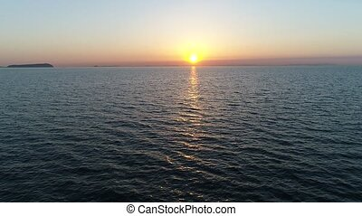 Aerial advance view of calm ocean at sunset, beautiful...