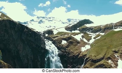 Aerial Alpine mountains, waterfall, snow cap. Mount Rainier and alpine meadows from the Skyline Trail. Aerial view of Myrtle Falls Mountain Wilderness with Wooden Bridge on Mount Rainier. Blue sky above jagged, Water falls in Mount Rainier