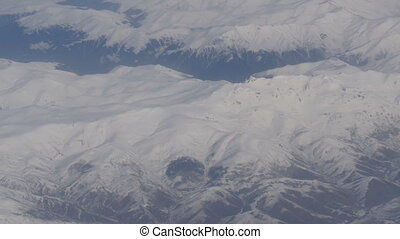Aerial and video shooting of snow-capped Caucasian mountains from the airplane