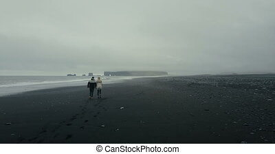 Aerial back view of the young couple in icelandic sweater walking on shore of the sea on black volcanic beach in Iceland